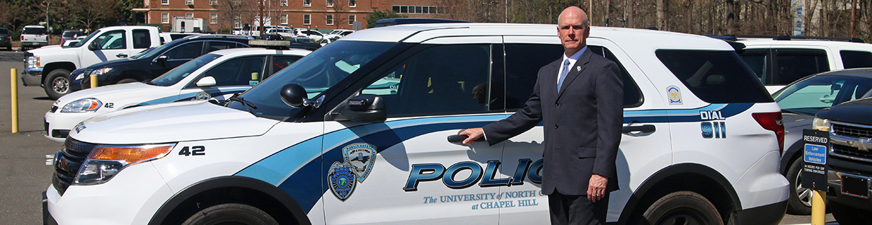 Jeff McCracken, Chief of Police, poses next to a UNC Police vehicle