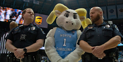 Police officers with Ramses Mascot at a UNC basketball game